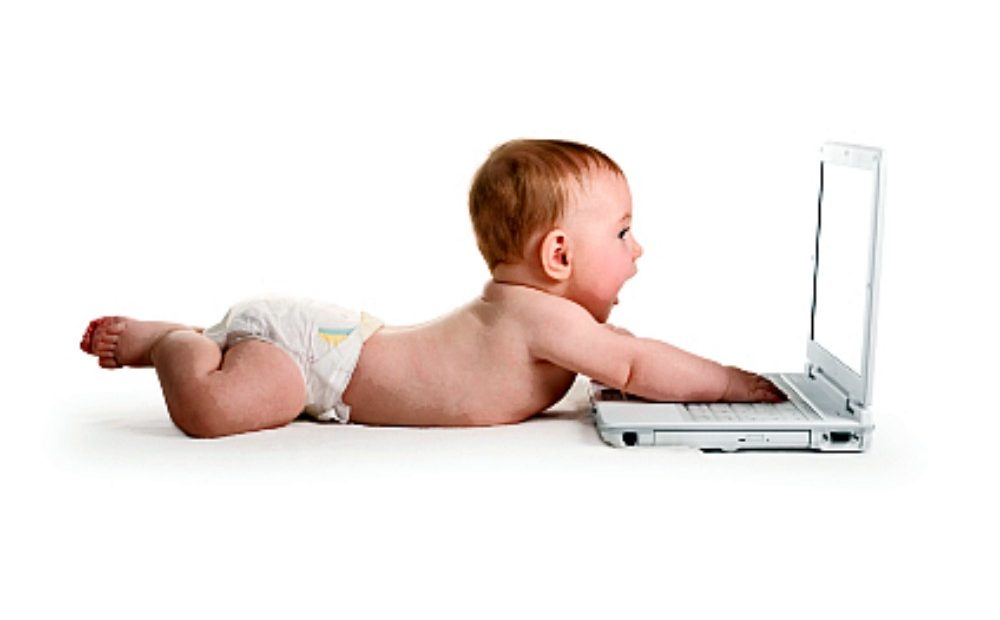 """A baby playing with a laptop"""